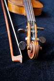 Violin scroll and bow on black velvet — Stock Photo