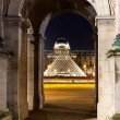 Louvre Pyramid though Arc in Paris - Stock Photo