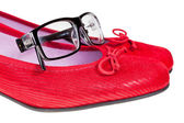 Red women's shoes and black eyeglasses — Stock Photo