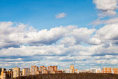 Urban panoramic landscape with spring clouds — Stock Photo