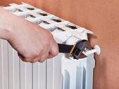 Adjusting heating radiator — Stock Photo