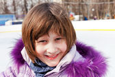 Smiling girl on rink in sunny winter day — Stock Photo