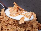 Spoon with yogurt and corn flakes — Stock Photo