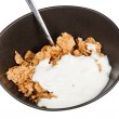 Yoghurt and spoon into bowl of cereal — Stock Photo