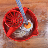Textile mop in red bucket — Stock Photo