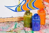 Målning och flaskor med färgämnen — Stockfoto