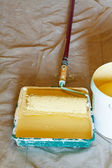 Paint tray with yellow emulsion paint — Stock Photo