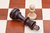 Standing and fallen chess king and pawn — Stock Photo
