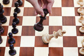 Hand with Black King hits white king — Stock Photo
