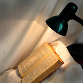 Book on pillow lit reading lamp — Stock Photo