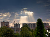Sun rays through clouds illuminate new buildings — Stock Photo