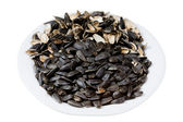 Sunflower seeds and husks on plate — Stock Photo