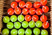Red and green candles in woven basket — Stock Photo