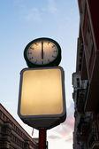 Street clock and blank advertising billboard — Photo