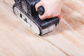 Finishing wooden surface by hand-held belt sander — Stock Photo