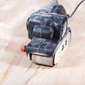Hand-held belt sander finishing wooden surface — Stock Photo