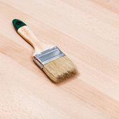 Paint brush on beech wooden board — Stock Photo