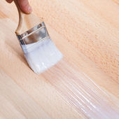 Putting lacquer on surface of beech top table — Stock Photo