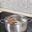 Simmering chicken broth on cooker — Stock Photo