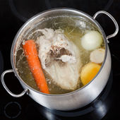 Top view of boiling chicken broth in pan — Stock Photo