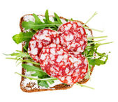 Sandwich from bread, cheese, salami and arugula — Stock Photo