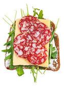 Sandwich from bread, salami, cheese, fresh rucola — Stock Photo