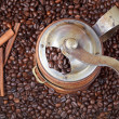 Retro manual coffee mill on roasted beans — Stock Photo #37183303