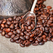 Roasted coffee beans and copper pot — Stock Photo