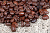 Many roasted coffee beans on sacking — Stock Photo