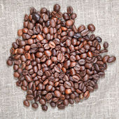 Handful of roasted coffee beans on textile — Stock Photo
