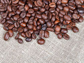 Many roasted coffee beans on cloth — Stock Photo