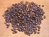 Roasted coffee beans on wooden board — Stock Photo