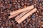 Cinnamon bark on roasted coffee beans — Stock Photo