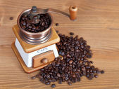 Heap of coffee and vintage manual mill — Stock Photo