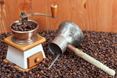 Coffee grinder and copper pot on roasted beans — Stock Photo
