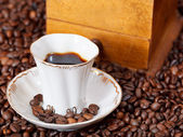Cup of coffee and roasted beans — Stock Photo