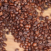 Roasted coffee beans close up on wooden board — Stock Photo