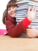 Schoolgirl, schoolwork and stack of books — Stock Photo