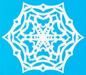 White snowflake on blue paper — Stock Photo