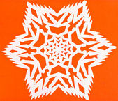 White snowflake on orange paper — Foto de Stock
