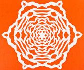 White snowflake on orange paper — Stock fotografie
