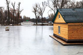 Frozen lake with bridge and wooden house — Stock Photo