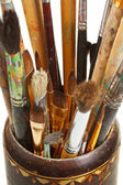 Used artistic paintbrushes in wooden cup closed up — Stock Photo