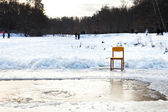 Icebound chair near opening water in frozen lake — Stockfoto