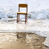 Icebound chair on edge of ice-hole in frozen lake — Stock Photo
