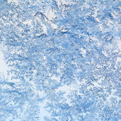 Snowflakes and frost pattern on glass close up — Photo