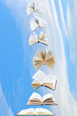 Stack of books fly in blue sky — Stock Photo