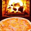 Постер, плакат: Pizza with prosciutto cotto and open fire in stove