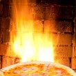 Постер, плакат: Pizza with prosciutto cotto and fire flame in oven