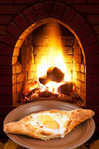 Adzharian khachapuri with egg and fire in stove — Stock Photo